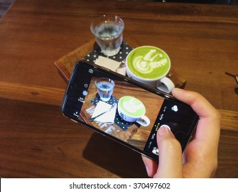 woman hand take a photo by mobile camera on set of a cup of milk hot green tea and water glass on wooden plate