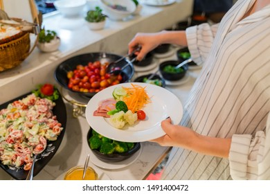 Woman hand taking food in buffet