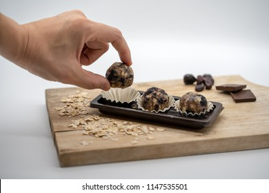 Woman hand taking healthy energy ball from the plastic tray on white background. Homemade no bake recipe.