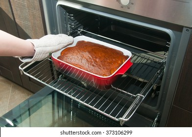 Woman hand taking out hot pie from the oven