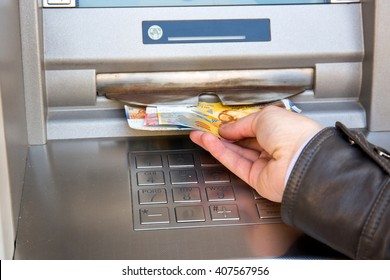 woman hand taking out swiss franc banknotes from atm