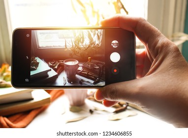 woman hand taking photo of  Autumn still life for muslim tradition m. cup of coffee,  orange scarf and maple leaves, holy book quran and rosary, siwak, oud perfume  on wooden background
