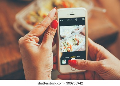 woman hand taking photo food by mobile phone vintage color filter tone