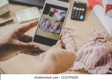 woman hand taking picture of her handmade product by smart phone for selling online