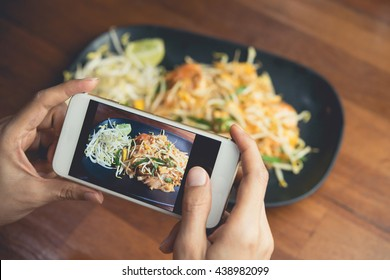 Woman hand taking Thai food photo by mobile phone. Food photography. Share food photography. Popular food photo.