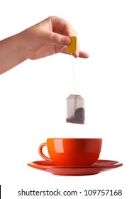 Woman hand with teabag and red cup isolated on white background