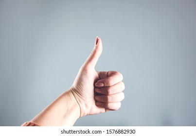 woman hand thumb on the gray background