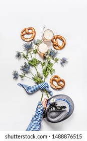 Woman hand in traditional blue shirt holding buch of alpine flowers on white background with pretzel and mugs of beer , top view. Oktoberfest concept. Modern layout. Flat lay