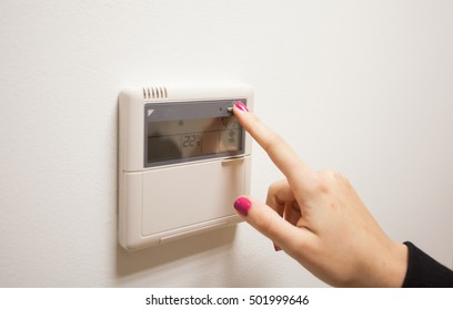 Woman hand turning on air condition panel