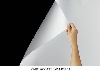 Woman hand turning page of paper, Blank sheet of paper on black background with clipping path. Change concept.