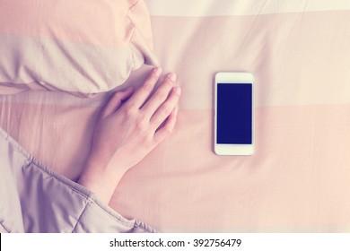 Woman hand under blanket being woken by mobile phone in bedroom.