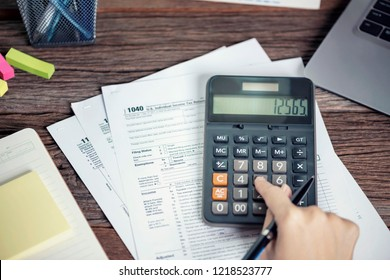 Woman hand using calculator Individual income tax return, taxation without representation, writing U.S. tax form 1040, time to payment concept.