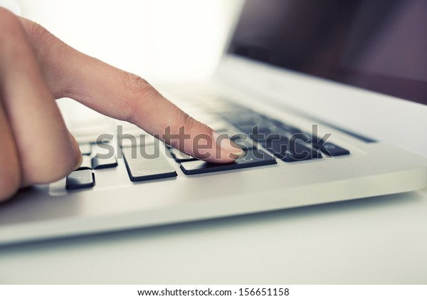 Woman hand using computer keyboard, enter button