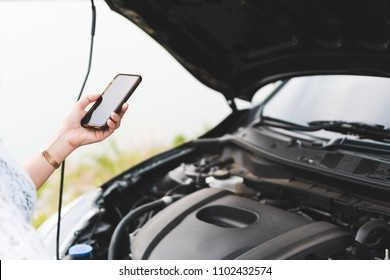 Woman hand using mobile phone with a broken car to call assistance on roadside. Accident and breakdown with auto, Road trip and travel problems, Car insurance concept.