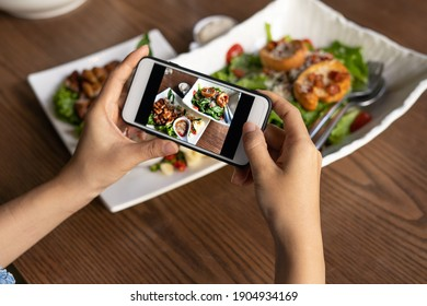 The woman hand is using a mobile phone to take a picture of food on the dining table in the restaurant.  Photography with Mobile Phone Concepts - Shutterstock ID 1904934169