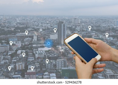 Woman hand using mobile smartphone searching location on map and pin above blue tone city scape and network connection, internet of things, satellite navigation system app, smart journey concept