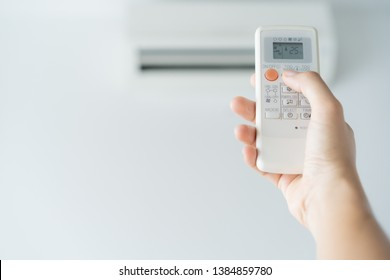 Woman hand using remote control open air conditioning 25 degrees. Open air 25 degrees, is temperature, save energy