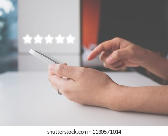 Woman hand using smart phone with icon five star symbol to increase rating of company concept