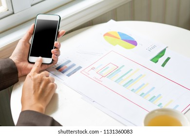 woman hand using smart phone while analyzing financial and stock graph