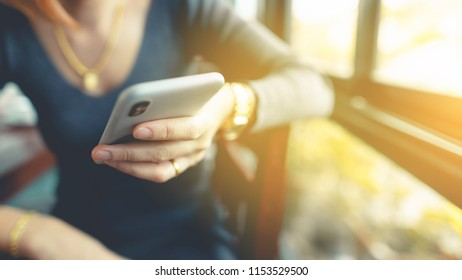Woman hand using smart phone while sitting in coffee shop during free time.woman hand holding mobile phone.vintage tone background, woman on phone concept