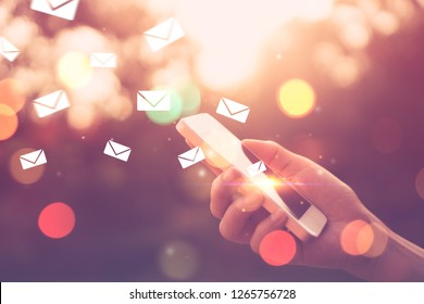 Woman hand using smart phone at outdoor nature park with sunset sky and email drawing flying abstract background. Copy space technology business and travel nature holiday concept. Vintage tone color.