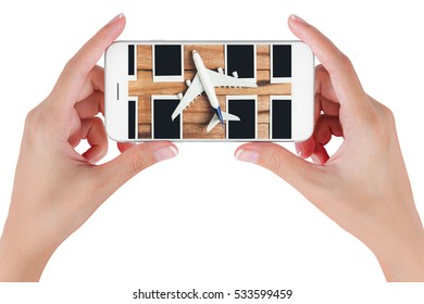 Woman hand using smart phone searching preparation traveling with airplane and photo frame on vintage wooden. Travel concepts, Isolated on white background.