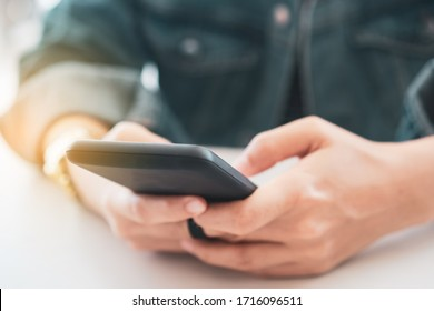 Woman hand using smartphone to do work business, social network, communication in public cafe work space area.