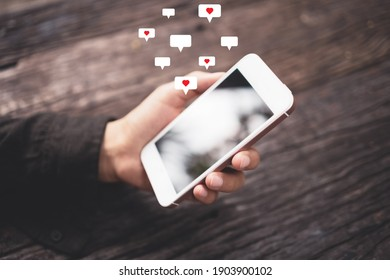 Woman hand using smartphone with heart icon at coffee shop background. Technology business and social lifestyle concept. Vintage tone filter effect color style.