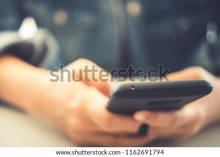 Woman hand using smartphone and laptop with cafe shop colorful highlight shade to object beautiful background. Business, financial, trade stock maket and social network concept.