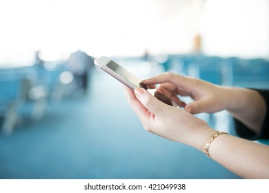 Woman hand using smartphone on background of blue chair waiting room at a international airport with busy traveler