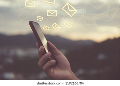 Woman hand using smartphone to send and recieve email for business on bokeh vintage color tone background.