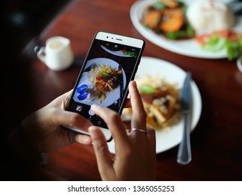 woman hand using smartphone take photo food in cafe