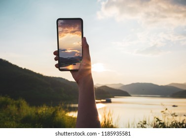 Woman hand using smartphone taking a photo of the sunset with clipping path.
