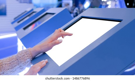 Woman hand using white blank interactive touchscreen display of electronic multimedia in dark room - scrolling and touching - close up view. Mock up, copyspace, template and technology concept