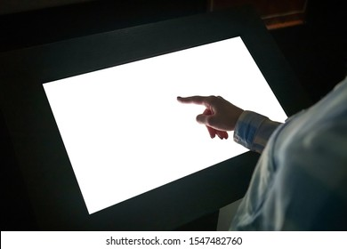Woman hand using white blank interactive touchscreen display of electronic multimedia kiosk in dark room - scrolling and touching - close up view. Mock up, copyspace, template and technology concept