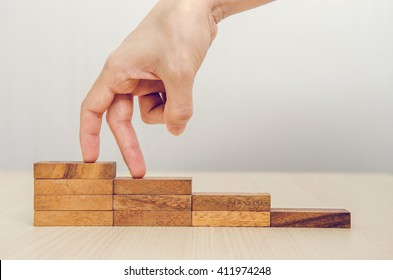 Woman hand walking his fingers up wooden steps on the way to success and aspiration.