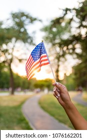 Woman hand is waving US flag outdoors on the Independance day during the sunset.