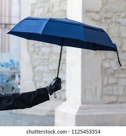 Woman hand wearing leather glove holding blue open umbrella in the city