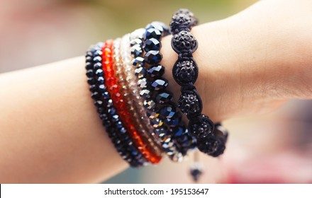 Woman hand wearing trendy colorful handmade bracelets.