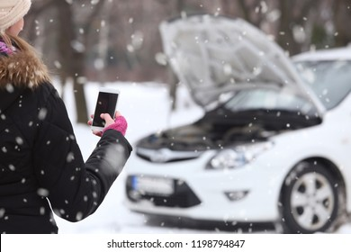 Woman hand in woolen gloves holding blank screen smart phone. Broken car in background.