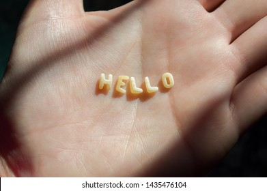 woman hand with the word hello made with word sopa, means soup, letters of alphabet of pasta for kids soup food