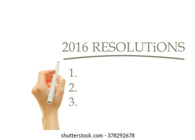 Woman hand writing 2016 RESOLUTIONS List on a transparent wipe board