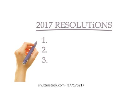 Woman hand writing 2017 Resolutions on a transparent wipe board