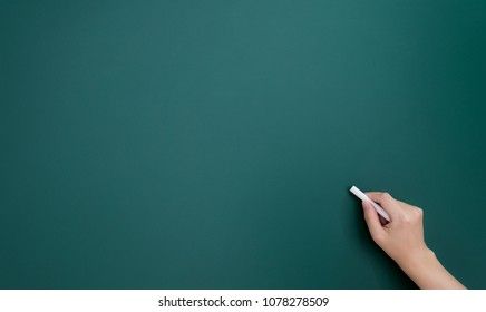 Woman hand writing by chalk on blackboard