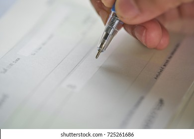 woman hand writing check, checque or cheque with ballpoint pen .to pay money for   fertilizer company  in next month.