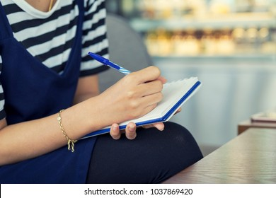 Woman hand writing check list on notebook, memo planning concept.