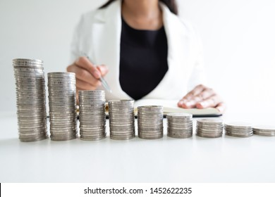 woman hand writing coins from her coins bar graph, step up growing business to success and saving for retirement concept.