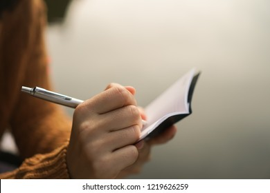 Woman hand writing down in small white memo notebook for take a note not to forget or to do list plan for future.