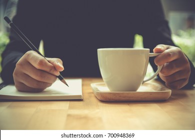 woman hand writing note on sketchbook holding coffee cup on table in cafe Close up. Female hand write on book, Designer, artist drawing sketchbook by pencil. note book on wooden table in coffee shop.