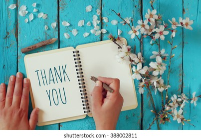 woman hand writing a note with the text thank you on a notebook, over wooden table and cherry blossom flowers